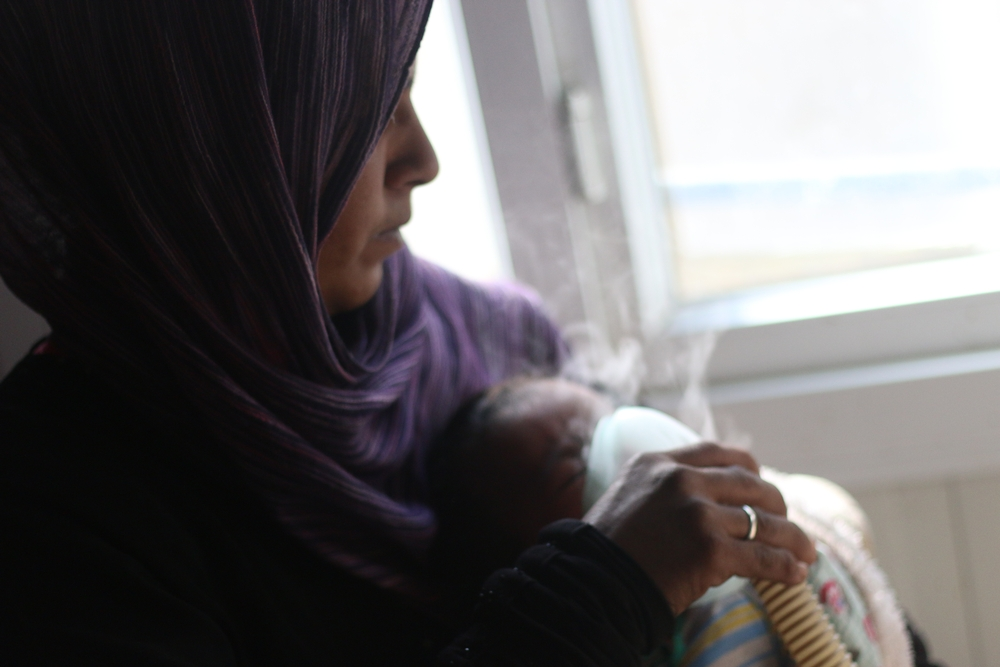 A mother gives her baby treatment on a nebulizer in this picture taken in MSF's hospital on 18 March in Azaz district.