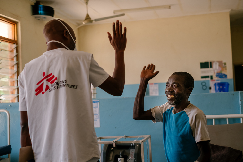 MSF Information Education and Communication Manager, Moses Luhanga, high fives a patient at Nsanje District Hospital in Malawi.