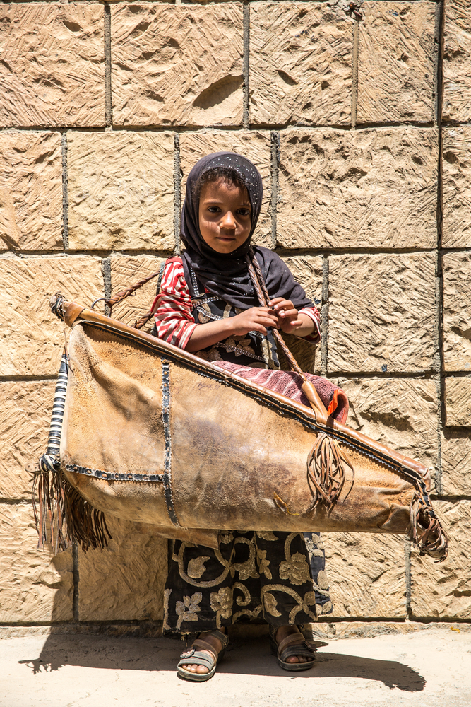 Abeer, 4, wears a bag in which he carries his 3-month-old sister Yasmine, who suffers from acute aqueous diarrhea. Haydan, Yemen, March 2018.
