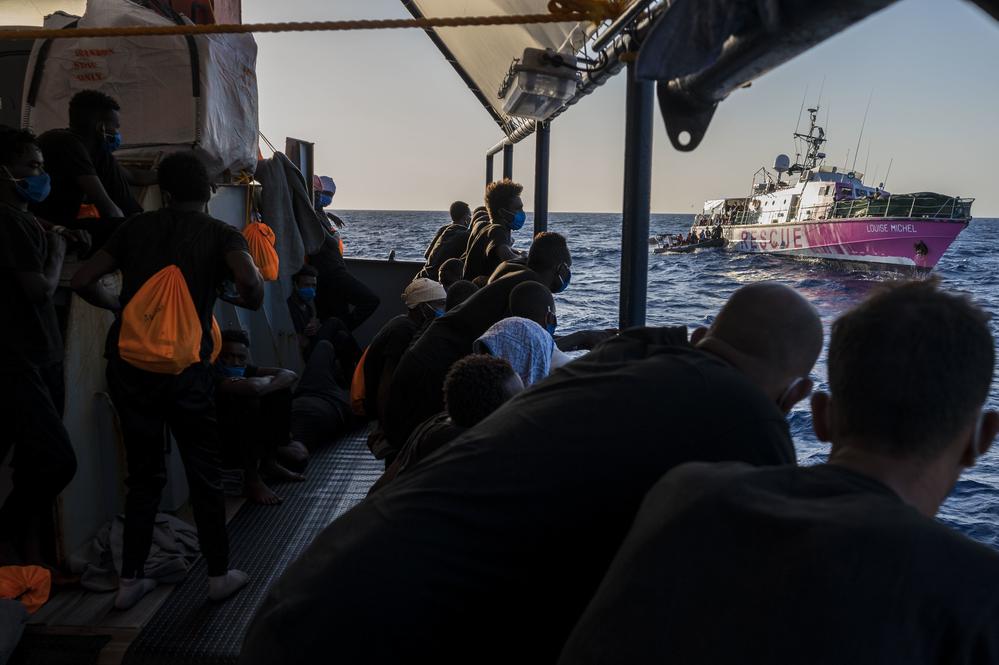 Des gens à bord d'un bateau regardent passer un navire de sauvetage à sa droite.