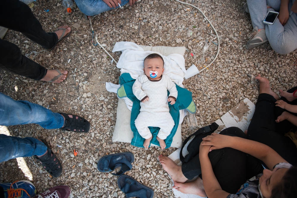 A Syrian baby lies in the floor of Kara Tepe camp. The family has no milk to feed the child.