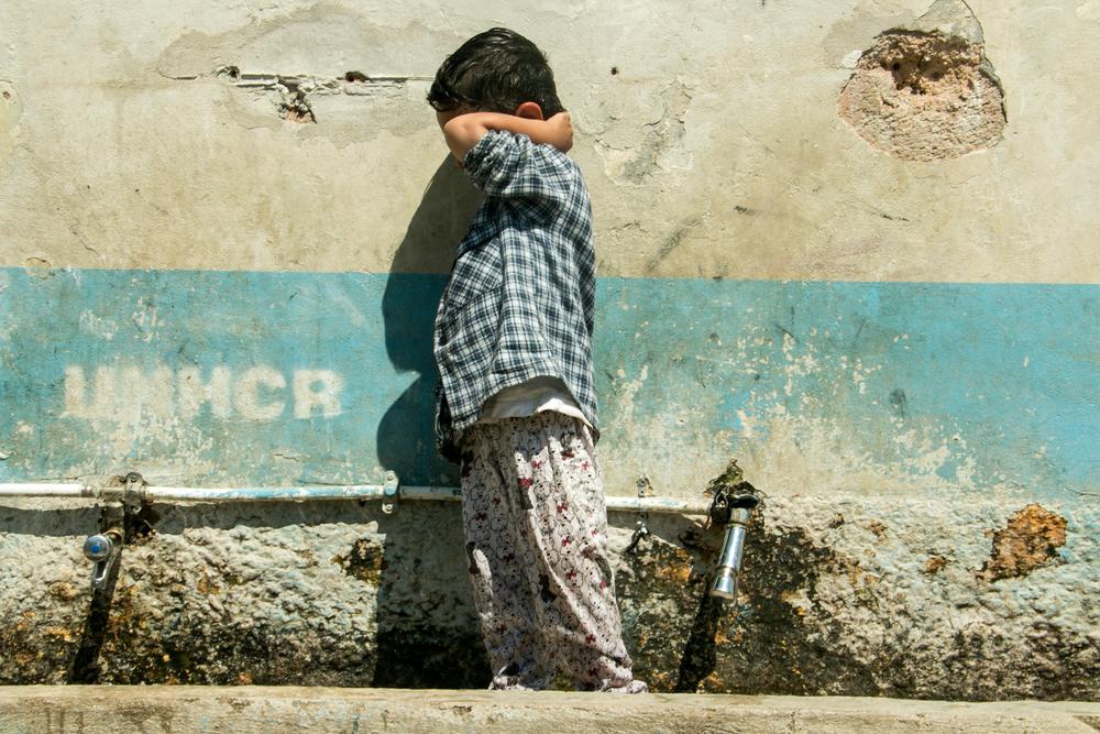 Un jeune enfant debout avec les mains autour de la tête devant un mur.