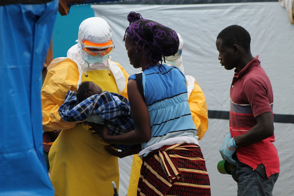 A Doctors Without Borders staff member in a Ebola protective suit hands over an infant to a woman in Liberia.