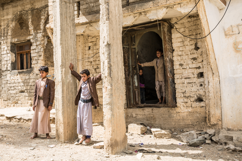 Ghani family children posing in front of the entrance of their house, bombed during the war of Saada between 2004 and 2010. Haydan, Yemen, March 2018.