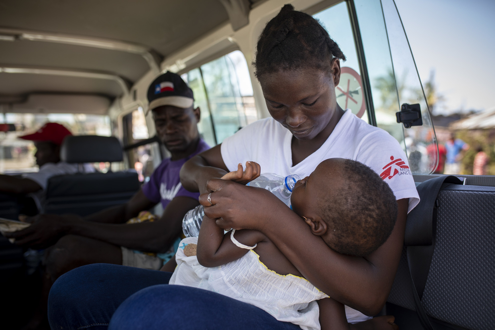 An MSF staff member evacuates a child suspected of suffering from pneumonia in Praia Nova, Beira area, during the response to Cyclone Idai.