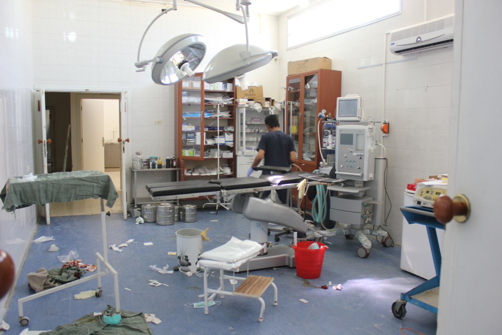 Operating room following a surgery with man in scrubs searching in a cabinet of medicine