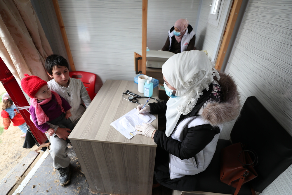 An MSF nurse wearing a face mask talks with a young boy, who has brought one of his relatives for a consultation at MSF's mobile clinic in an IDP camp in Northwest Syria.