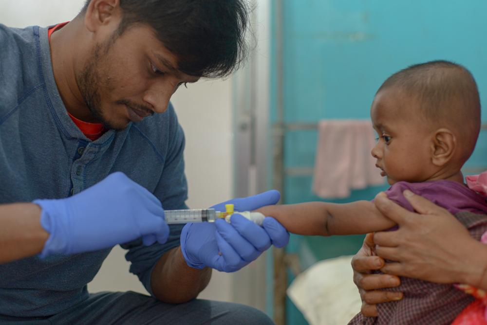 Un infirmier de MSF insère une canule sur un bébé