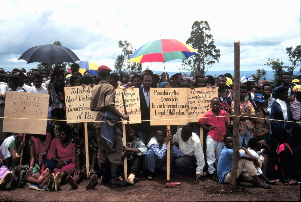 Tutsi survivors of the genocide at the one year anniversary of the genocide. Beneath umbrellas.
