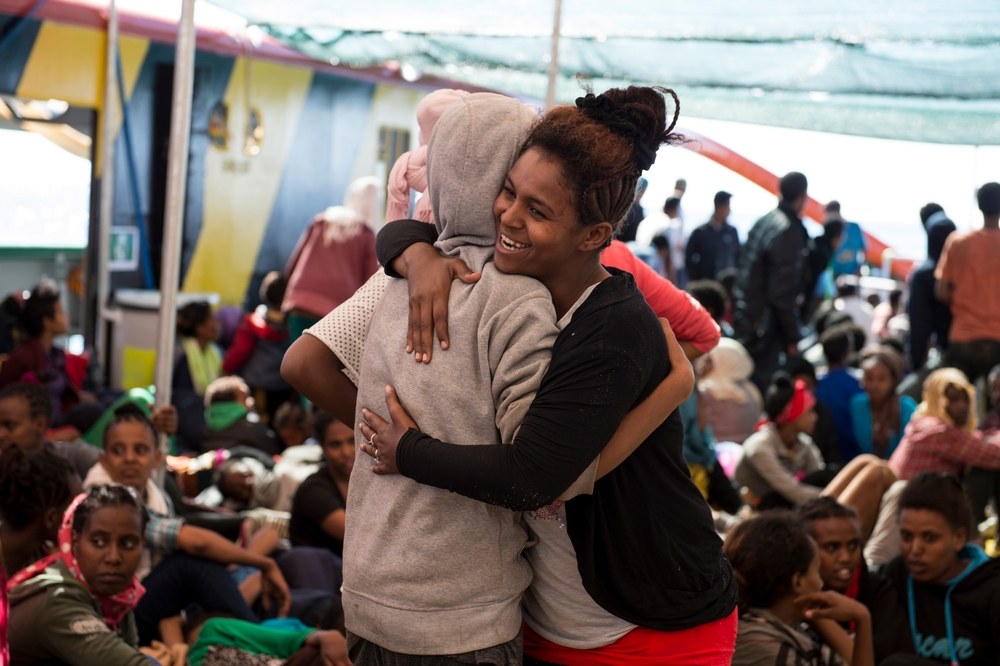 Two rescued woman hug each other after being rescued by the Bourbon Argos on 13 May.