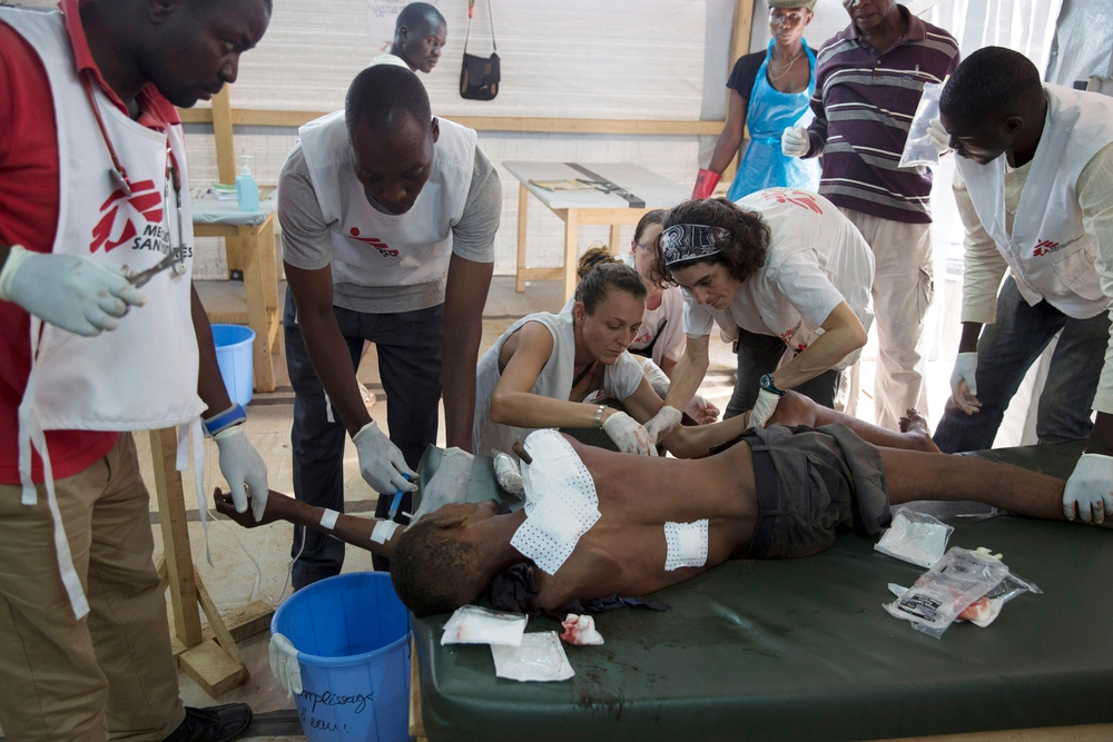 MSF medical staff treating a man in Mpoko airport camp who was hit by an arrow.