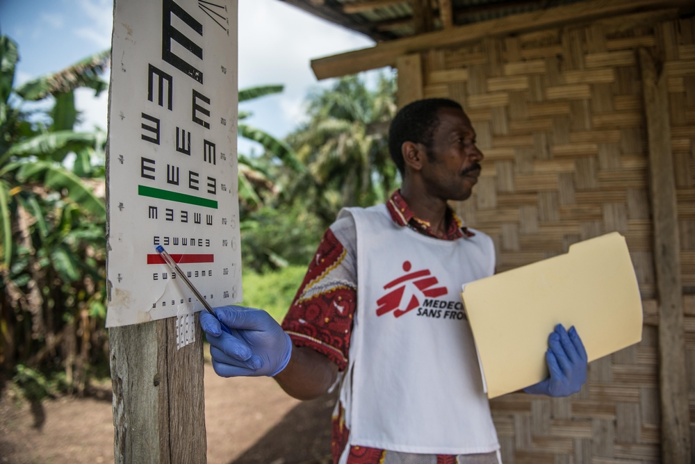Health promoter Joseph Fofana conducts an eye test with an Ebola survivor during an MSF outreach mission the village of Mabekoh.