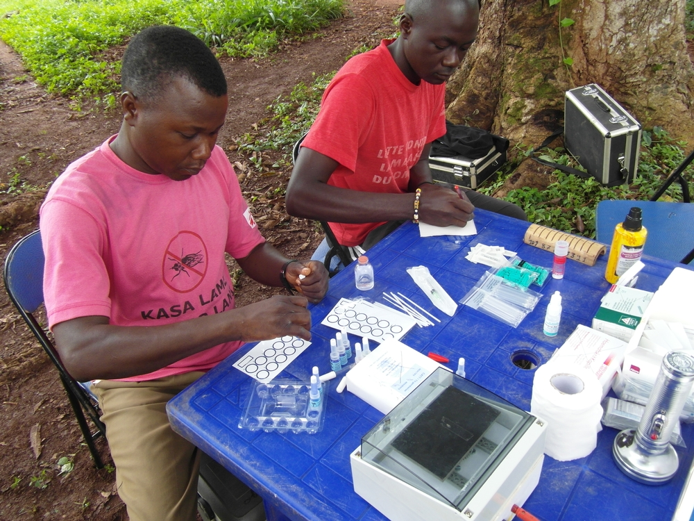 The MSF team sets up a diagnostic table and prepares to test villagers in Sukadi.