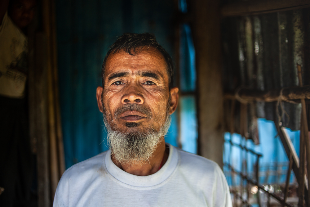 Suleiman stands by the entrance to his home in Nget Chaung village. Nget Chaung is an area comprising a village and a makeshift camp, it is remote, overcrowded, squalid and prone to floods during the rainy season. Nget Chaung home to approximately 9,000 p