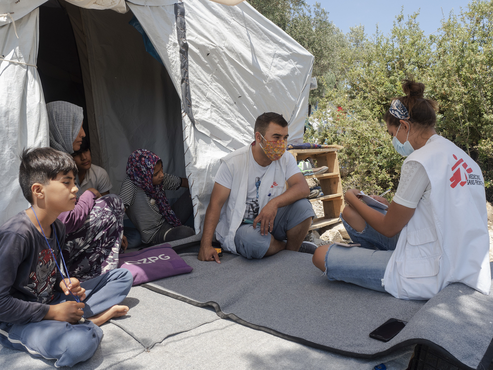 MSF staff speaking with a family from Afghanistan, still separated from two of their children who became lost while trying to re