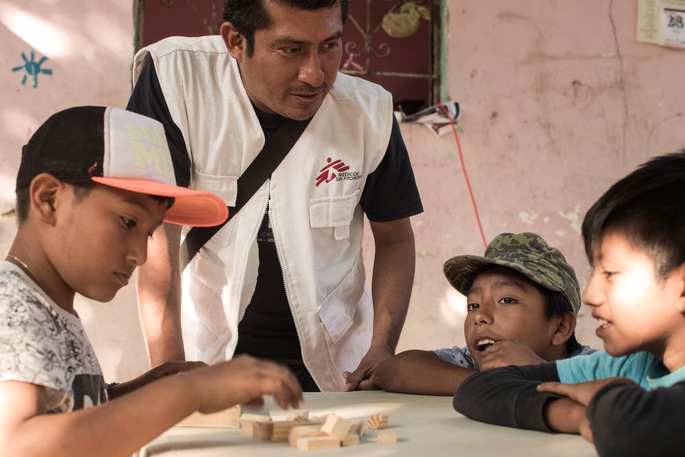 Un membre du personnel MSF et trois enfants en train de jouer avec des blocs.