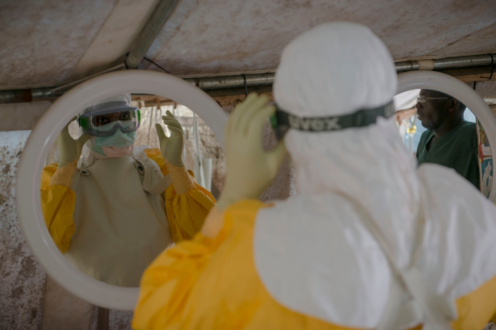 MSF staff dressing in personal protective equipment to enter the high risk zone at MSF Ebola management centre in Donka.