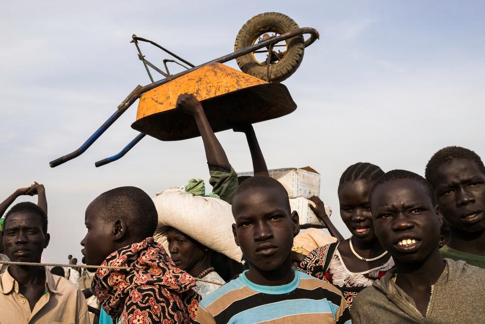 Tucty mladíků čekají, aby mohli vlastníma rukama či s využitím trakařů pomoci s distribucí jídla ze Světového potravinového programu v táboře Bentiu.