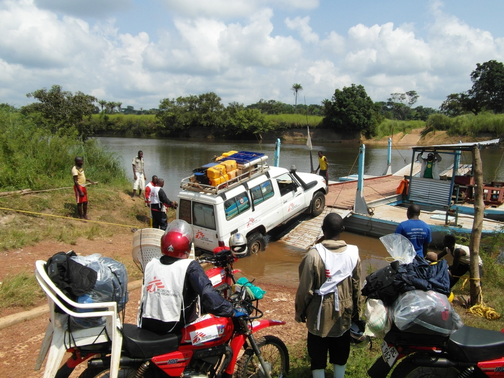 In order to reach target populations, it can take the team hours to board trucks and motorcycles on to a ferry to make a short river crossing.