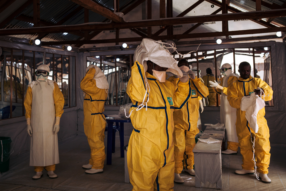 Health workers put on their personal protective equipment before entering the red zone of an Ebola treatment centre in North Kivu province, DRC.