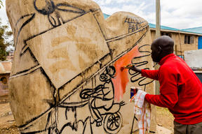 "Painting ""Tuko Poa"" benches in Kibera"