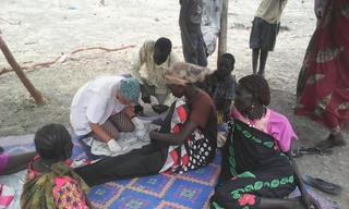 An MSF medic provides care to an IDP