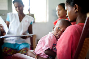 A mother and child sitting for a checkup at Pusalota health centre.