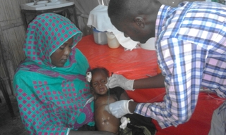 White Nile State, Sudan, Doctor examines child